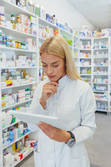 Woman pharmacist checking a medicine while holding a tablet in pharmacy drugstore