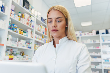 Beautiful young woman pharmacist at work looking at computer at pharmacy drugstore