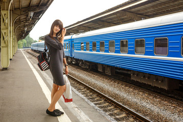 beautiful young woman standing on the platform of the railway station