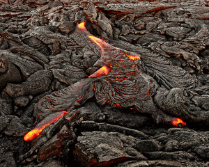 """A lava flow emerges from an earth crevice and flows in a black volcanic landscape, glowing magma, first daylight - Location: Hawaii, Big Island, volcano """"Kilauea"""""""