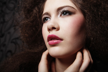 Beautiful young woman with curly hair and evening make-up. Jewelry and Beauty concept. Fashion art photo.