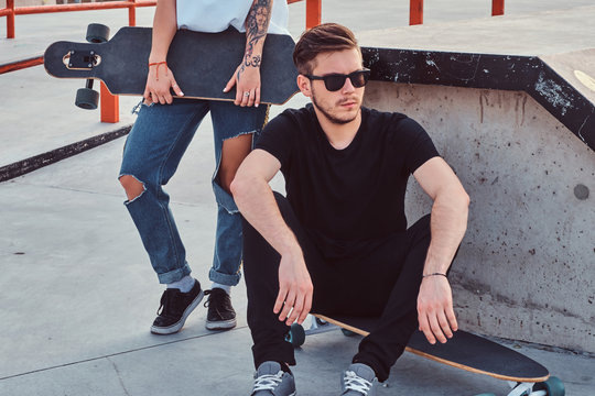 Portrait of a stylish hipster guy sitting on a longboard at a skatepark.