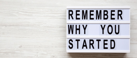 Lightbox with 'Remember why you started' words over white wooden background, overhead. Copy space.
