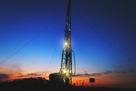 drilling rig drills a well for the extraction of drinking water at sunset under a beautiful sky for drinking people