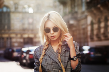 Outdoor close up fashion portrait of young beautiful woman wearing stylish sunglasses, wrist watch, gray tartan blazer. Model walking in street of european city. Copy, empty space for text