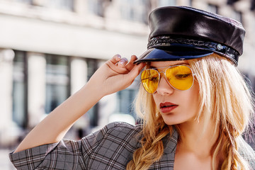 Outdoor close up fashion portrait of young beautiful woman wearing yellow aviator sunglasses, trendy leather cap, posing in street of european city