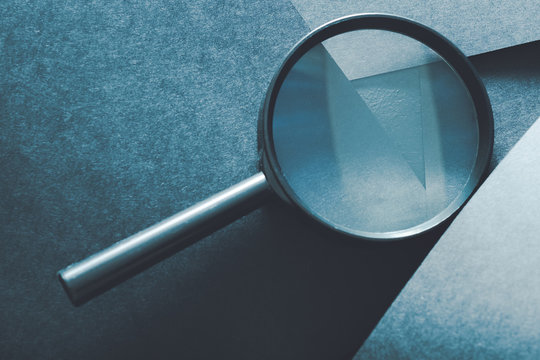magnifying glass. comparison assessment and analysis. loupe on layered blue paper background.