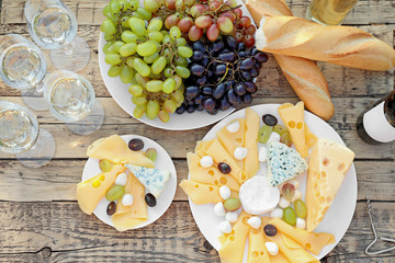 Wine, cheese and grapes on wooden table, top view. Vineyard picnic