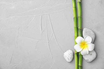 Tuinposter Frangipani Composition with bamboo branches, stones and plumeria on light background, top view. Space for text