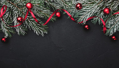 Horizontal black stone background with fir branches decorated with red balls. Top view. Space for text