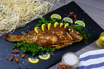 Delicious baked fish carp stuffed crust with vegetables on a shale board, cooking recipe. Top flat view, from above
