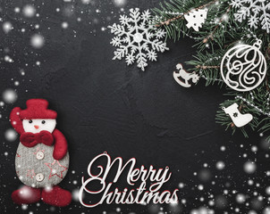Christmas greeting card on black stone background with a green fir tree with wooden toys. Horizontal top view. With space for yours text Merry Christma