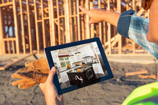 Female Construction Worker Reviewing Kitchen on Computer Pad at Construction Site