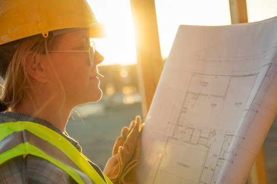 Female Construciton Worker with House Plans at Construciton Site