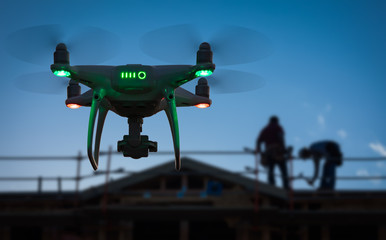 Silhouette of Unmanned Aircraft System (UAV) Quadcopter Drone In The Air at Construction Site