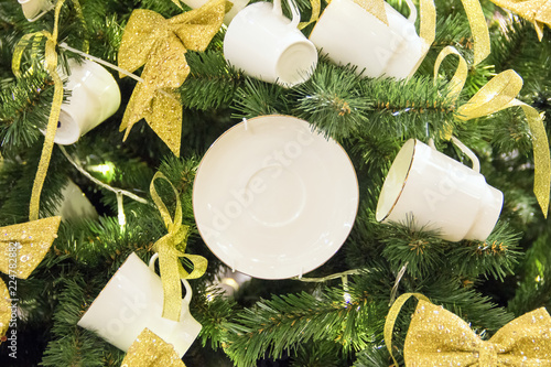 Christmas tree background and Christmas decorations. White porcelain tea cups and saucers with golden ribbons on green fir. Happy New Year and Xmas theme