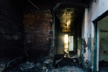 Sinister and creepy Corridor of abandoned hospital after fire. Ceiling in black soot