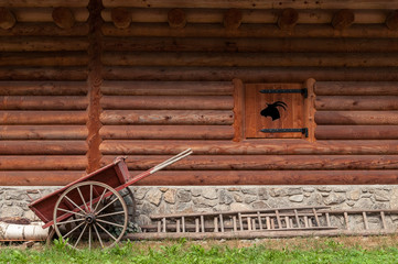 Wall of mountain cabin in wood with inlaid wooden box, a wooden wheelbarrow and a wooden staircase