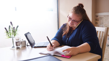 Plus size business woman busy multitasking at her local coffee shop to get as much work done as possible early in the morning, as she writes in her journal and talks on the phone simultaneously.