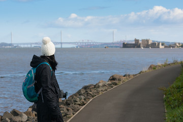 lady photographer looking on to blackness castle and the forth bridges in scotland