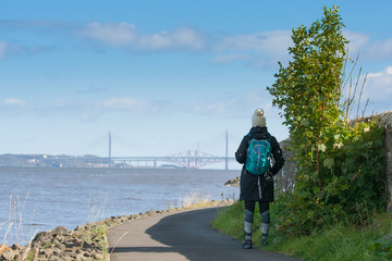 lady hiker looking on to forth bridges in scotland