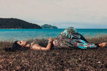 beautiful young boho woman lying on a grass at the beach