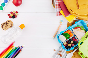 Lunch box on white wooden background near school accessories and backpack.jpg