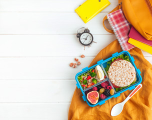 Lunch box on white wooden background near school accessories and backpack