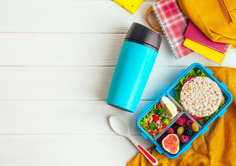 Photo sur Plexiglas Assortiment Lunch box on white wooden background near thermo mug and school accessories