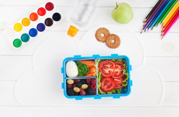 Lunch box with sandwich, vegetables, berries on white wooden background with school accessories