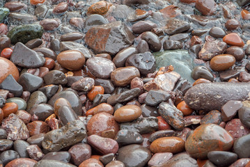 Colorful beach stones in the waves along the North Shore of Lake Superior, closeup, Minnesota, North Shore, background, texture