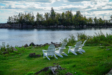 Tranquil scene with white wooden lawn chairs on green grass overlooking Lake Superior in Northern Minnesota
