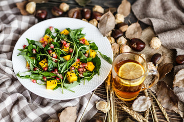 Food flat lay. Top view. Salad with mango, arugula, pomegranate seeds lying on white plate. Next lying pumpkin, cup of black tea with lemon, dry flowers and leaves, physalis, chestnuts, sweater
