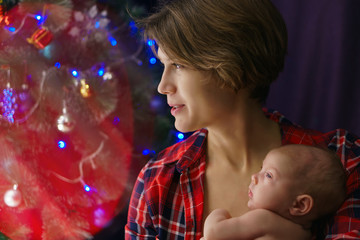 Family photo of young mother and newborn daughter close-up. In background lights are garlands and Christmas tree. Happiness of motherhood.