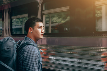 Young asian hipster man standing and waiting train on platform.