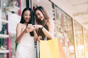 Two asian woman standing at store front with happy watching smart phone at shopping mall center.