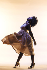 Woman giving in to dancing, wearing beautiful beige dress, isolated in studio