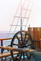 Travel by sea on a stylized old ship with a wooden steering wheel, masts, tackle