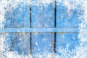 Old weathered wooden plank painted in blue color, wooden texture wall winter with snowflakes snow effect christmas background. Concept holidays symbol for Merry Christmas, New Year