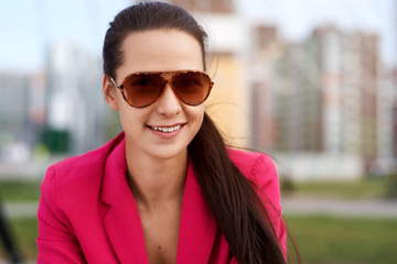 An attractive young brunette woman in a bright red jacket and sunglasses smiles cute. Large facial portrait and snow-white smile
