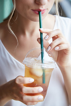 Cropped image of young woman enjoying drinking refreshing iced tea with straw