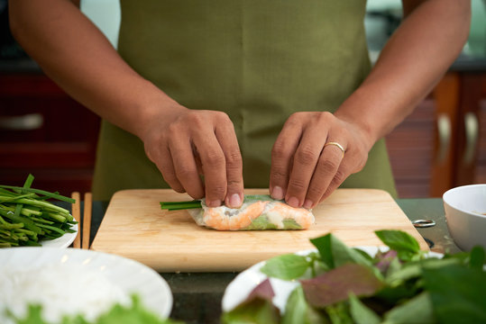 Man making traditional Asian spring rolls with shrimp and vegetables