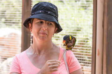 Young  woman feeds parrots at the Australian Zoo Gan Guru in Kibbutz Nir David, in Israel