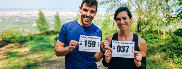 Smiling young man and woman showing their trail race number outdoors