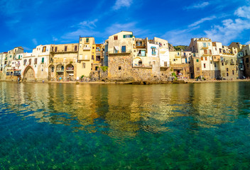 Cityscape of Cefalu village with traditional architecture reflected in water. Sicily island in Italy