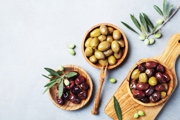 Pickled olives served in bowls from olive wood top view.