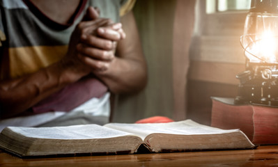 Close up Holy Bible with old woman praying background, christian concept.