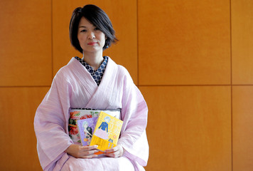 Yuki Ozawa, the comic book author of Sanju Mariko, poses with her comic books during an interview with Reuters in Tokyo