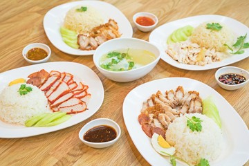Rice with roasted red pork + Crispy roasted belly pork chinise style on rice + Hainanese chicken rice , Thai gourmet steamed chicken with rice with soup. top view thai food on wooden table.