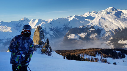 skier wearing winter equipment standinf in front od snowy mountain